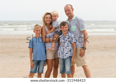 Happy smiling family with three children standing on the sunny beach. - stock photo