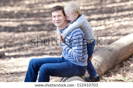 happy smiling father and his son sitting on a tree log - stock photo