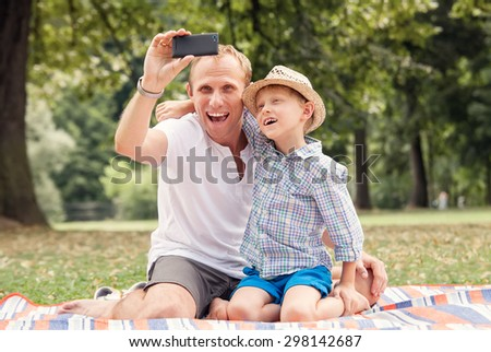 Happy smiling father and son take a self picture with a phone - stock photo