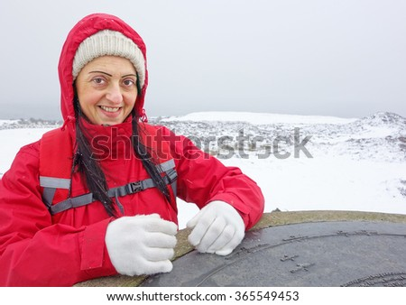 Happy, smiling female hiker at the summit of Brown Clee Hill in winter snow, the highest peak in Shropshire, England, UK.  - stock photo