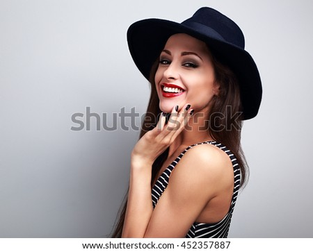 Happy smiling female model in black elegant hat on blue background - stock photo
