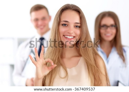 Happy smiling female patient with two cheerful doctors in the background. Medical and health care concept  - stock photo