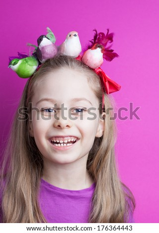 Happy smiling five years old blond caucasian child girl with colorful birds on head - pastel purple background. Careless childhood, vacation and spring concept. - stock photo
