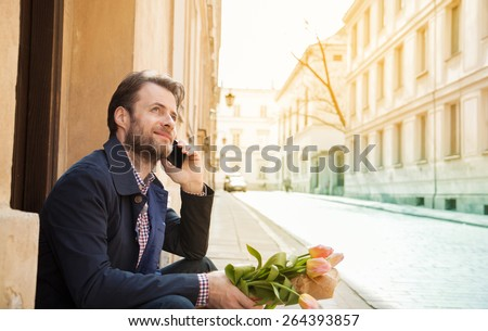 Happy smiling forty years old caucasian man with flower bouquet talking on a mobile phone. Street and city buildings as background. - stock photo