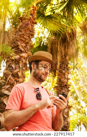 Happy smiling forty years old caucasian tourist man looking at mobile phone outdoor among exotic palm trees - summer holiday traveling - stock photo