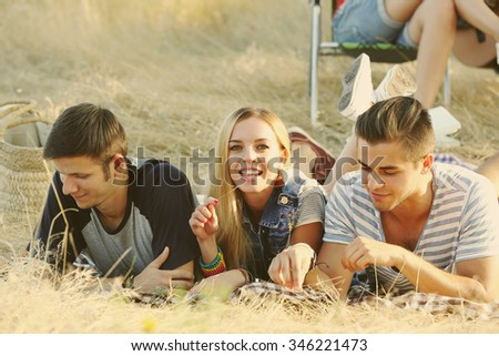 Happy smiling friends lying in the forest outdoors - stock photo