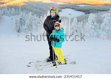 Happy smiling girl  and with her mother in ski goggles and helmets on the top of the hill with beauty view of Ruka. finland - stock photo