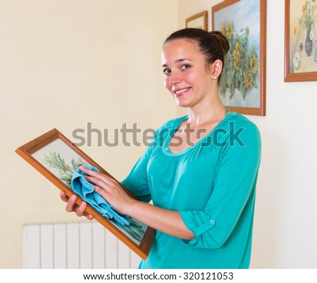 Happy smiling girl dusting the picture indoor - stock photo