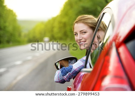 Happy smiling girl in a red car. At sunset. Travel concept. - stock photo