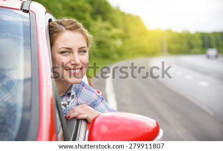 Happy smiling girl in a red car at sunset. Travel concept. - stock photo