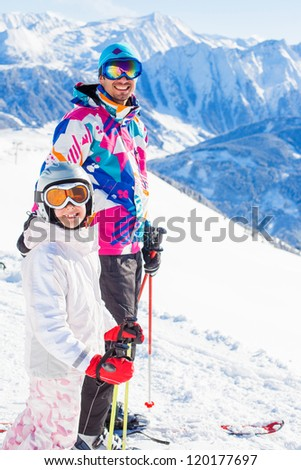 Happy smiling girl in ski goggles and with her father, Zellertal, Austria. Focus on the girl - stock photo