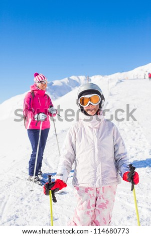 Happy smiling girl in ski goggles and with her mother, Zellertal, Austria - stock photo