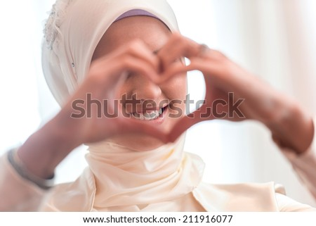 Happy smiling girl making heart symbol with her hands - stock photo