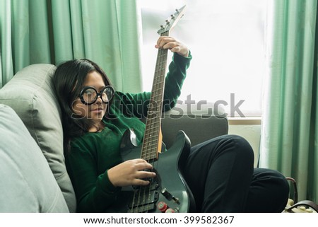 Happy smiling girl ,wearing glasses,learning to play the Bass guitar at home laying on sofa  - stock photo