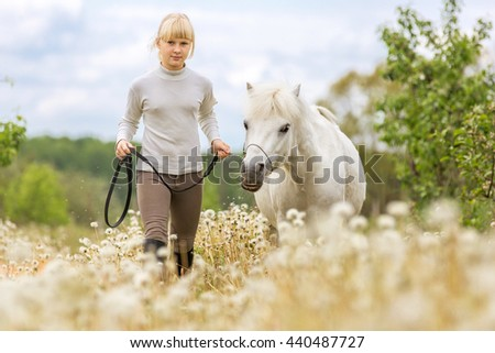 Happy smiling girl with a white pony - stock photo