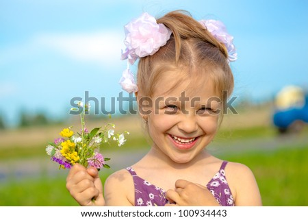 Happy smiling girl with flowers relaxing outdoor - stock photo