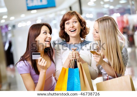 Happy smiling girls with credit cards in shop - stock photo