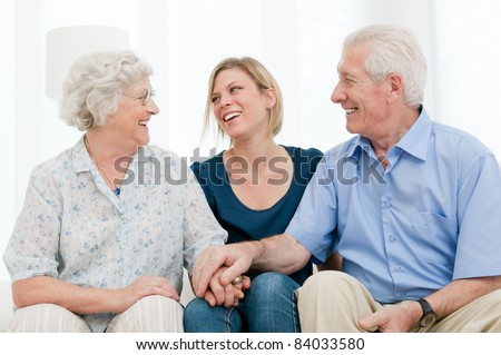 Happy smiling granddaughter staying with her grandparents at home - stock photo