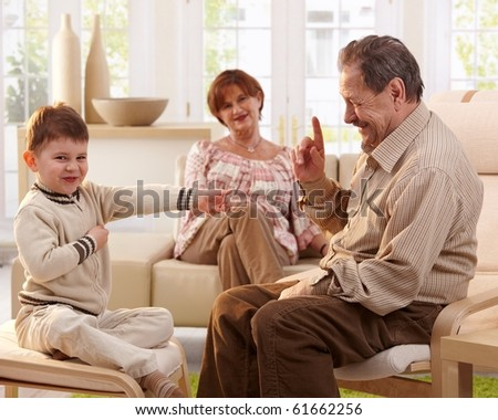 Happy smiling grandfather telling a story to his grandchild, grandmother listening in background.? - stock photo
