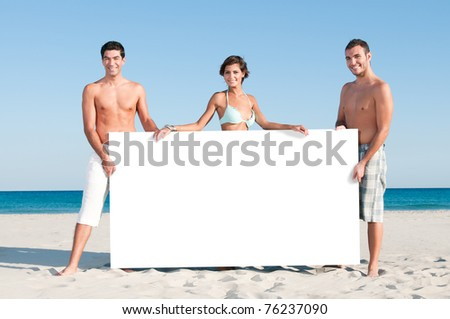 Happy smiling group of friends holding a white board for your text at summer beach - stock photo