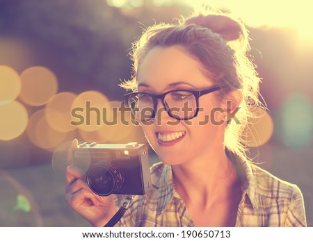 Happy Smiling Hipster Girl in Glasses Taking a Photo with Vintage Camera. Toned Photo with Bokeh. Modern Youth Lifestyle Concept. - stock photo