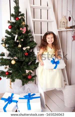 Happy smiling kid holding gifts near the Christmas tree. Christmas, New Year, holiday concept, ready for your text, letters, logo or symbols. - stock photo