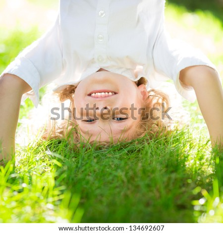 Happy smiling kid playing on green grass in spring park. Healthy lifestyle concept. Children`s fitness - stock photo