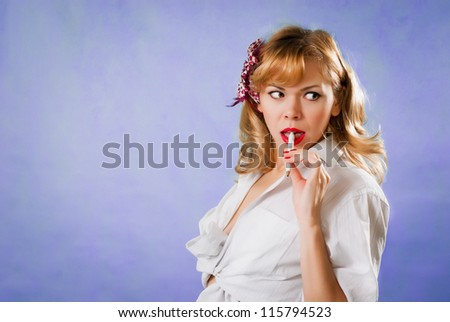 Happy smiling l thinking young business woman with pen in pinup style on blue background - stock photo