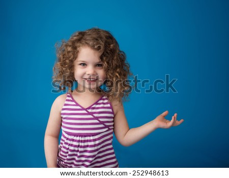 Happy smiling laughing child looking at camera: girl with curly hair holding or pointing at something - stock photo