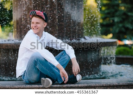 happy smiling laughing teen boy in the park sitting on the fountain background close up portrait - stock photo