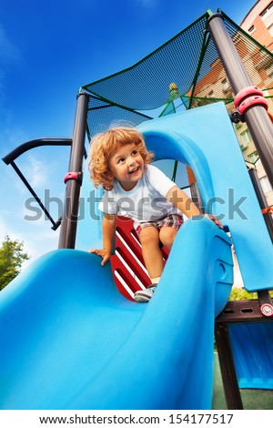 Happy smiling little boy about to slide on blue playground - stock photo