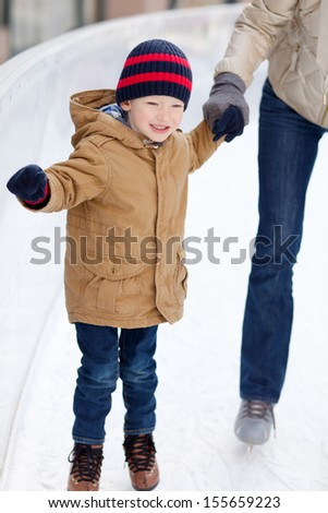 happy smiling little boy ice skating and holding his parent - stock photo