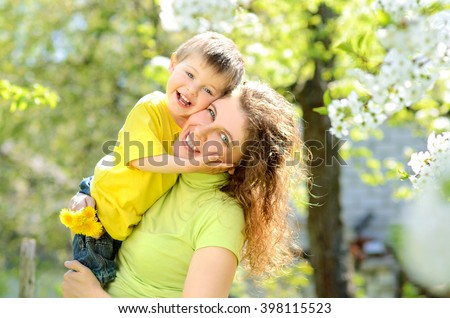 Happy smiling little boy in the arms of his mother in the lush spring garden apple - stock photo