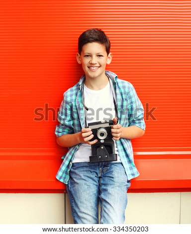 Happy smiling little boy teenager with retro vintage camera in city over red background - stock photo