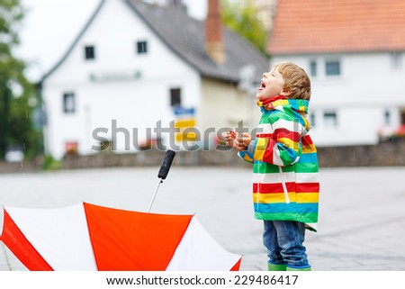 Happy smiling little boy walking in city and playing with red umbrella, wearing colorful rain coat and green boots outdoors at rainy day. Catching raindrops with mouth. - stock photo