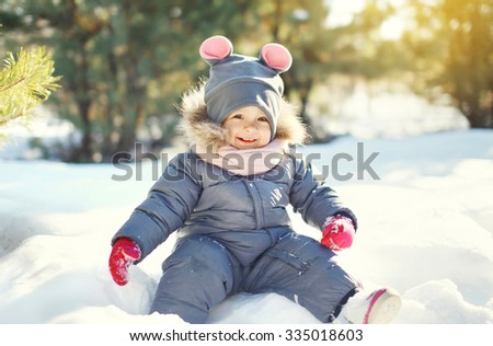 Happy smiling little child playing on snow in winter day - stock photo