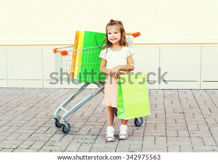 Happy smiling little girl child and trolley cart with colorful shopping bags in city - stock photo