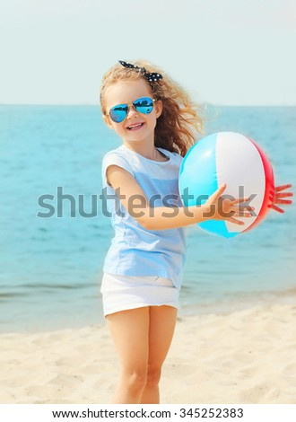 Happy smiling little girl child playing with inflatable water ball on beach near sea summer - stock photo