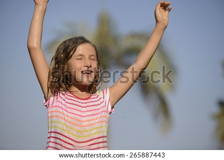 Happy smiling little girl happy outdoor in a sunny day enjoying the light rain. - stock photo