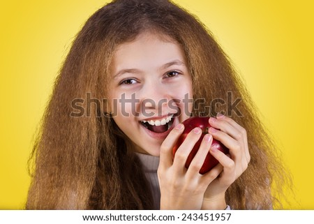Happy, smiling little girl holding an red apple, eating it isolated on yellow background.Healthy food,Dental health. - stock photo