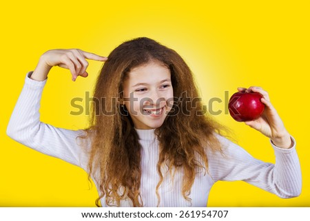 Happy, smiling little girl holding an red apple, pointing with finger to her head isolated on yellow background.Healthy food,Healthy Thinking,Positive thinking.Idea. - stock photo