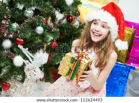 happy smiling little girl in Christmas pink hat with gifts near decorated new year tree - stock photo