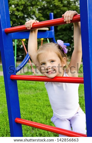 Happy smiling little girl on outdoor playground equipment - stock photo