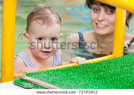 happy smiling little girl with mother at water pool - stock photo