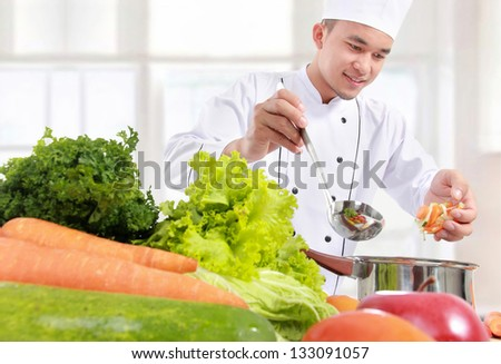 happy smiling male chef cooking put some ingredient in the pot - stock photo