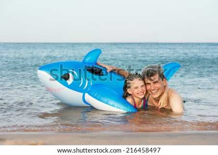 Happy smiling man and child playing in red sea water - stock photo