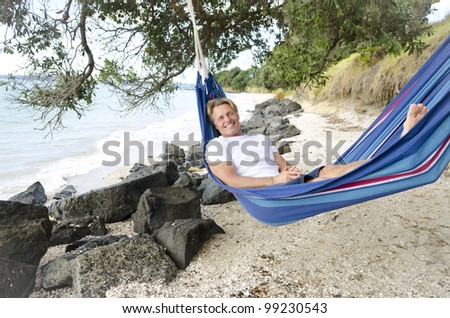 happy smiling man in hammock relaxing on the beach. - stock photo