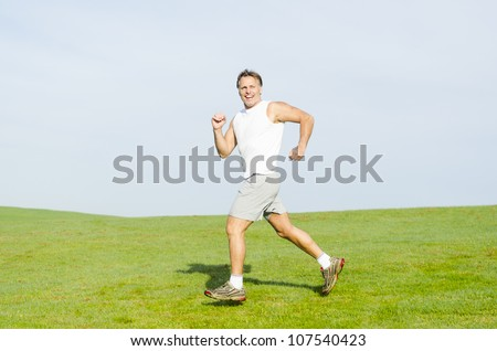 happy smiling man running in a park wearing a white tank top and grey shorts. - stock photo