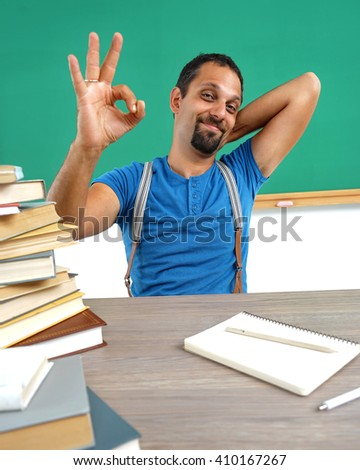 Happy smiling man showing okay gesture. Photo of smiling teacher, creative concept with Back to school theme - stock photo