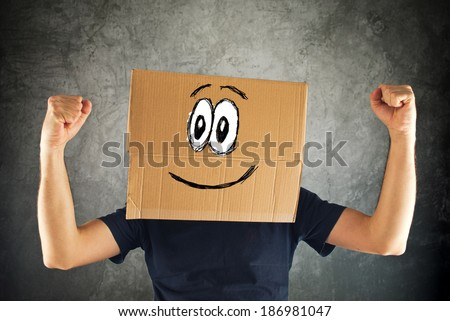 Happy smiling man with cardboard box on his head and raised fists for victory. Concept of winning. - stock photo